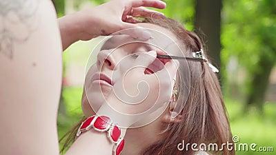 A menina com olhos verdes olha acima e compõe o artista continua a aplicar-se compõe Movimento lento video estoque