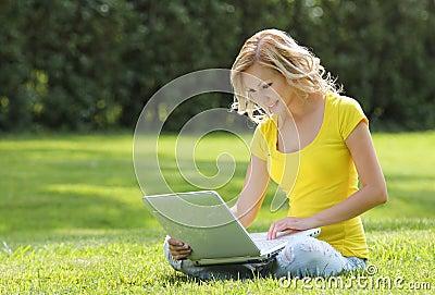 Menina com portátil. Jovem mulher bonita loura com o caderno que senta-se na grama. Exterior. Dia ensolarado