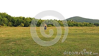 A menina corre afastado A menina corre afastado na frente da câmera Menina que corre no campo Menina com cabelo curly longo Vista filme
