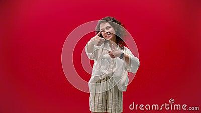 A menina curly se diverte e mostra legal em um sorriso de fundo vermelho. filme