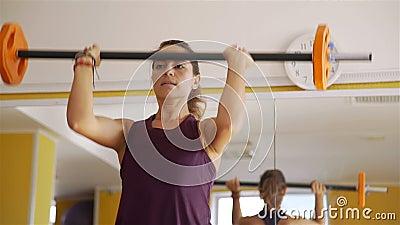 Menina da aptid?o que exercita com o barbell no gym video estoque