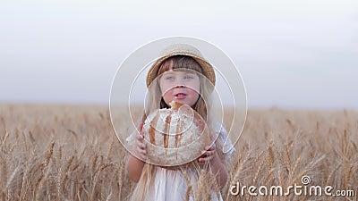 A menina da criança do cultivador do pão, filha de cabelo justa pequena do fazendeiro morde o pão cozido saboroso e os sorrisos q video estoque