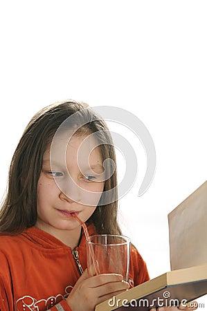 Menina da leitura com vidro do suco