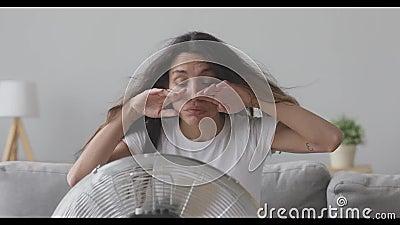 Menina de raça mista sobreaquecida sentada em frente ao ventilador filme