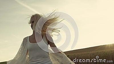 A menina de sorriso com cabelo bonito corre a cruz o campo do trigo dourado Movimento lento, tiros do estabilizador Alegria da vi vídeos de arquivo