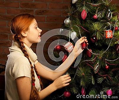 A menina decora a árvore de Natal