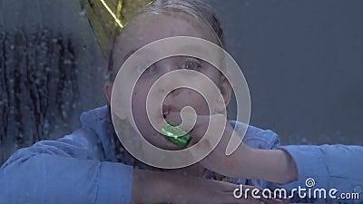 Menina deprimida que joga com o ventilador do partido atrás da janela chuvosa, vítima tiranizando vídeos de arquivo