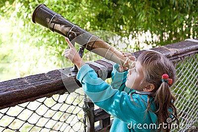 A menina descobre através do telescópio antiquado