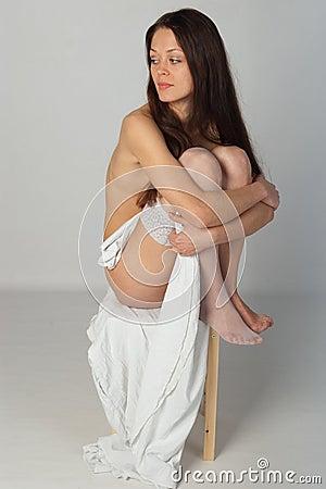Menina despida que senta-se no tamborete