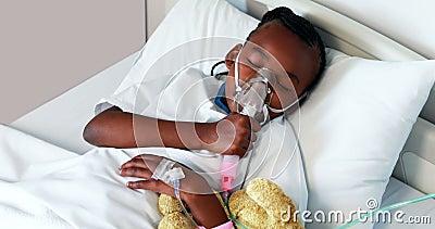 Menina doente na máscara de oxigênio que descansa com urso de peluche vídeos de arquivo