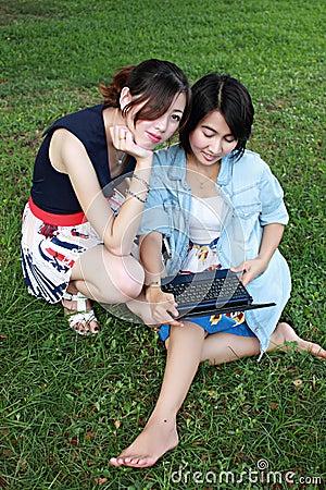 Menina dois bonita em um computador portátil ao ar livre.