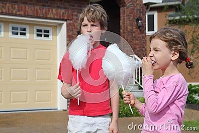 A menina e o menino comem doces de algodão