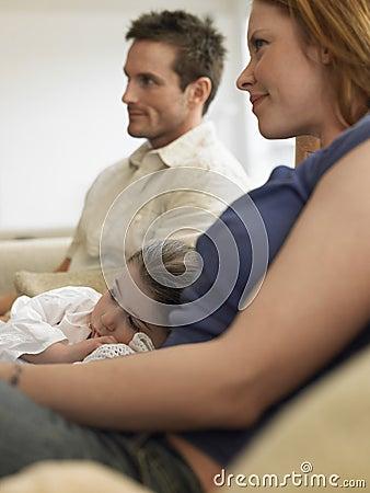 Menina e pais que olham a tevê em casa