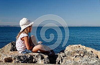 Menina em rochas do beira-mar