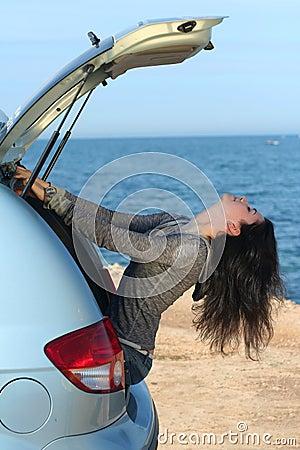 A menina em um portador de bagagem do carro