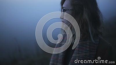 A menina em uma névoa grossa azul é triste vídeos de arquivo