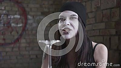 Menina emocional com a cara branca que senta-se na tabela na frente dos livros e do vidro de vinho nele, discutindo com um não id video estoque