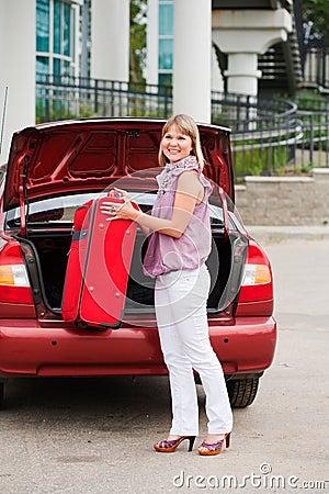 A menina empilha uma mala de viagem