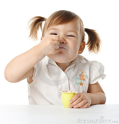 A menina engraçada come o yogurt