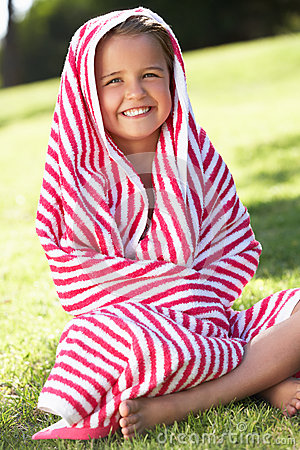 Menina envolvida na toalha que senta-se no jardim