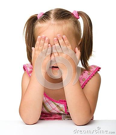 A menina está jogando o hide-and-seek