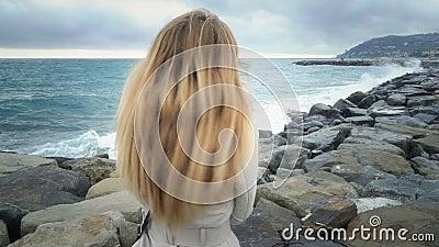 A menina está na praia durante a tempestade no mar vídeos de arquivo