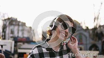 A menina está pondo sobre os fones de ouvido e está começando mover-se com os ritmos da música Nos óculos de sol Aprecie-o lento vídeos de arquivo