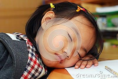 A menina está dormindo perto de seus trabalhos de casa