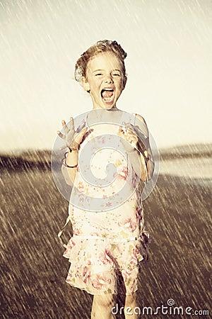 Menina feliz que funciona na chuva