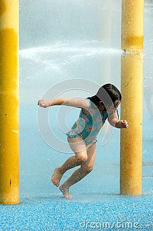 Menina feliz que joga com água