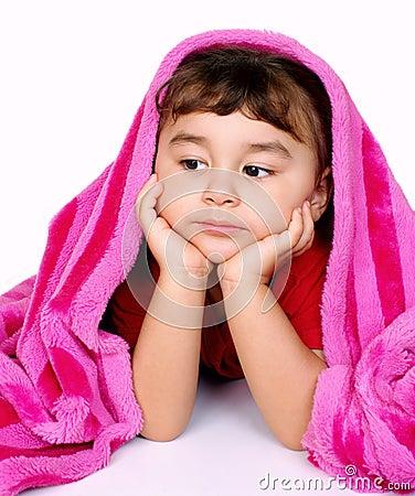 Menina furada sob o cobertor cor-de-rosa