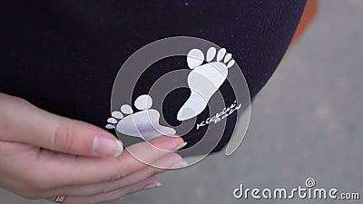 Menina grávida bonita em um t-shirt que afaga sua barriga em antecipação ao bebê vídeos de arquivo