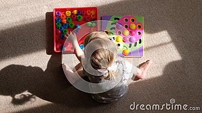 A menina joga um jogo de habilidades de motor tornando-se, recolhe um mosaico multicolorido para crianças, desenvolvimento do de filme