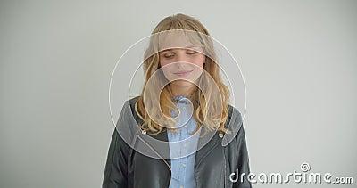 Menina loura bonita no casaco de cabedal que levanta na câmera com sorriso tímido isolada no fundo branco filme