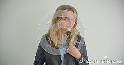 Menina loura bonita no casaco de cabedal que roda seu cabelo que olha na câmera que é tímido isolada no fundo branco filme