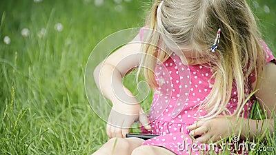 Menina loura bonito na idade pré-escolar que senta-se na grama verde que joga com telefone esperto video estoque