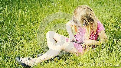 Menina loura bonito na idade pré-escolar que senta-se na grama verde que joga com telefone esperto vídeos de arquivo