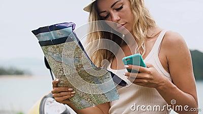 A menina loura em um chapéu, senta-se em uma bicicleta e olha-se o telefone e um mapa, olha a rota em Ásia filme
