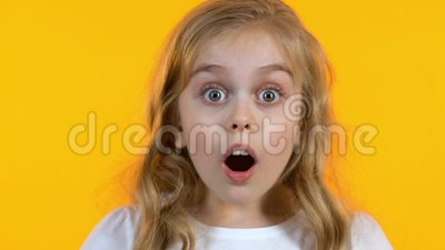 Menina loura que olha a not?cia extremamente chocada da audi??o, fundo amarelo isolado video estoque
