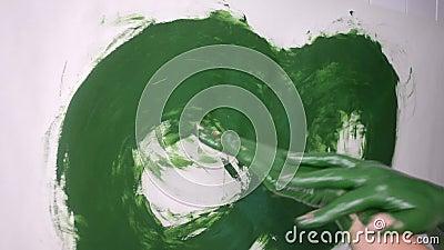 A menina mancha a pintura verde nas mãos e tira-a no papel filme