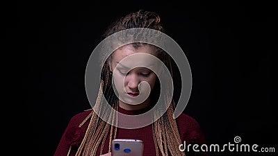A menina moreno extraordinária com dreadlocks olha atentamente no smartphone que está sendo concentrado no fundo preto vídeos de arquivo