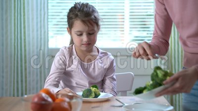 A menina não quer comer vegetais e não gostar do gosto dos brócolis e dos espinafres vídeos de arquivo