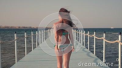 Menina no roupa de banho que anda no cais quando o vento fundir filme