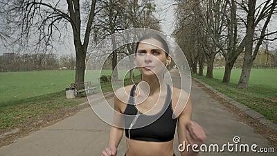 A menina nova do esporte está correndo com os fones de ouvido no parque no verão, estilo de vida saudável, concepção do esporte filme