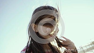 A menina pequena alegre está, grita, e corre em uma praia do mar, no por do sol no slo-mo video estoque