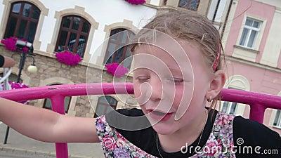 Menina pequena bonito na atração do funfair Carrossel do Funfair Menina feliz alegre que grita durante o passeio do carrossel filme