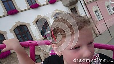 Menina pequena bonito na atração do funfair Carrossel do Funfair Menina feliz alegre que grita durante o passeio do carrossel 4K filme