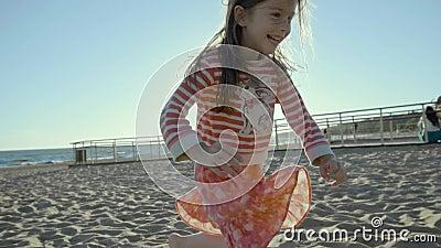 A menina pequena de riso corre ao longo da praia do mar ao tropeçar na areia no slo-mo vídeos de arquivo