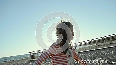 A menina pequena de sorriso está, corre, e salta em uma praia do mar, no por do sol no slo-mo filme