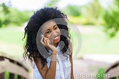 Menina preta adolescente que usa um telefone celular - pessoa africano
